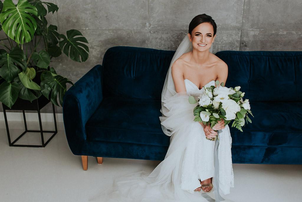 wesele sesja nad morzem uśmiechnięta panna młoda siedząca na sofie