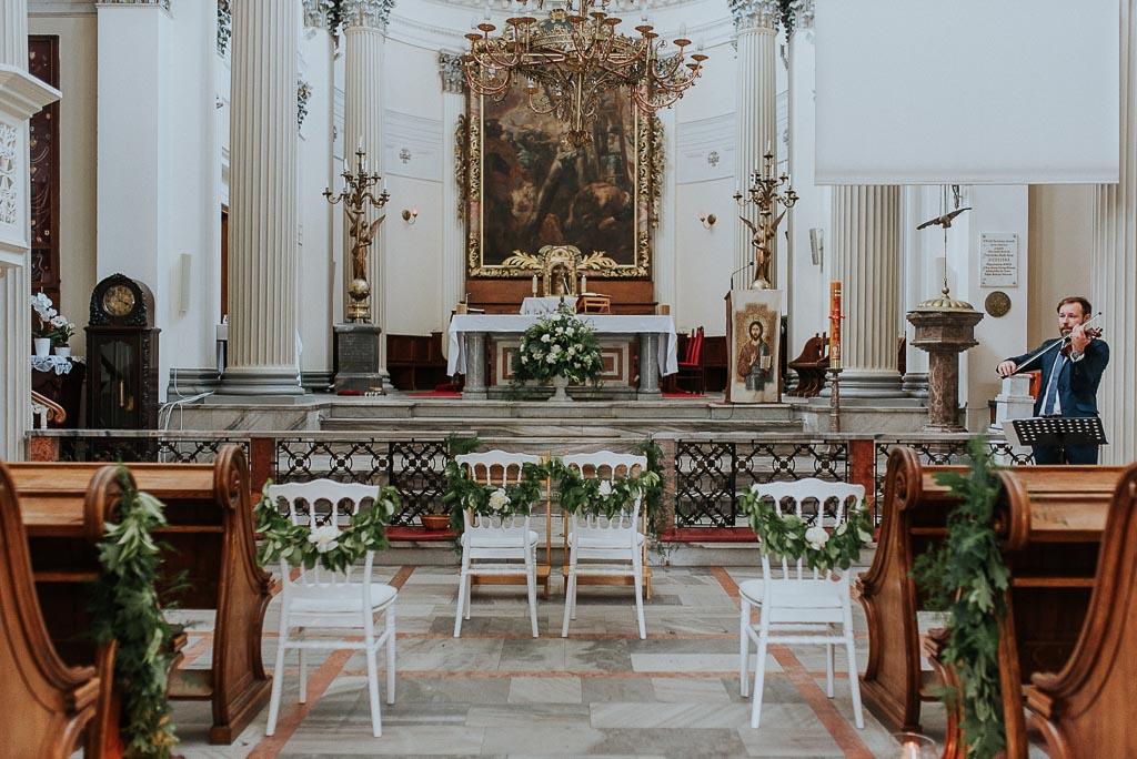 wesele sesja nad morzem ozdobione białe krzesła w kościele skrzypek na ślubie