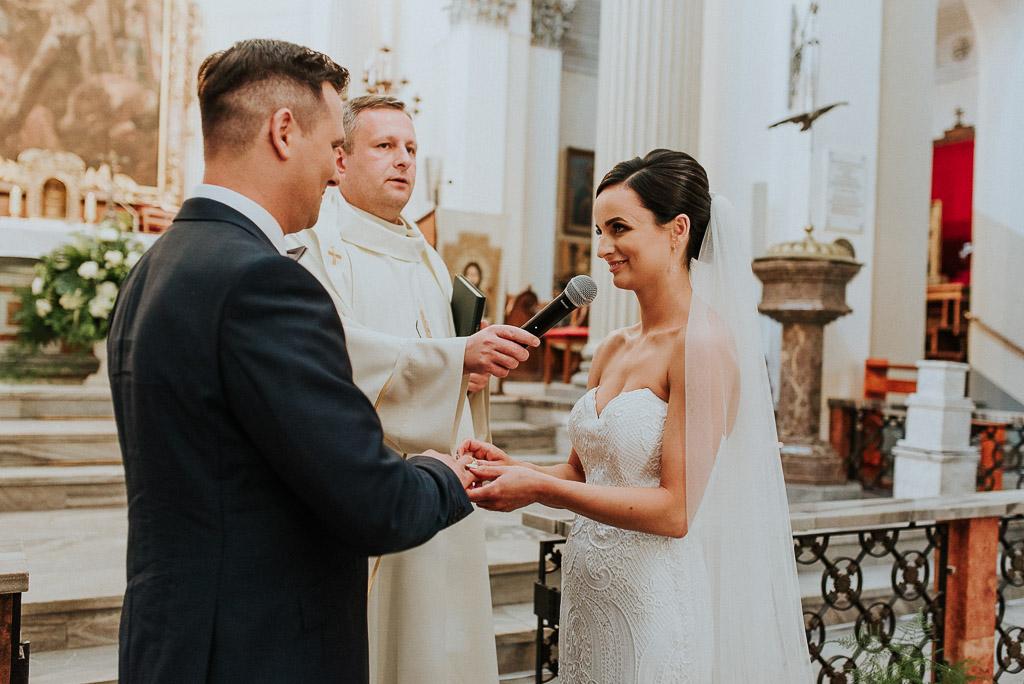 wesele sesja nad morzem panna młoda wkłada obrączkę na palec pana młodego