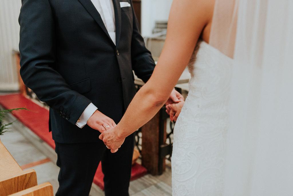 wesele sesja nad morzem nowożeńcy trzymają się za ręce pod ołtarzem