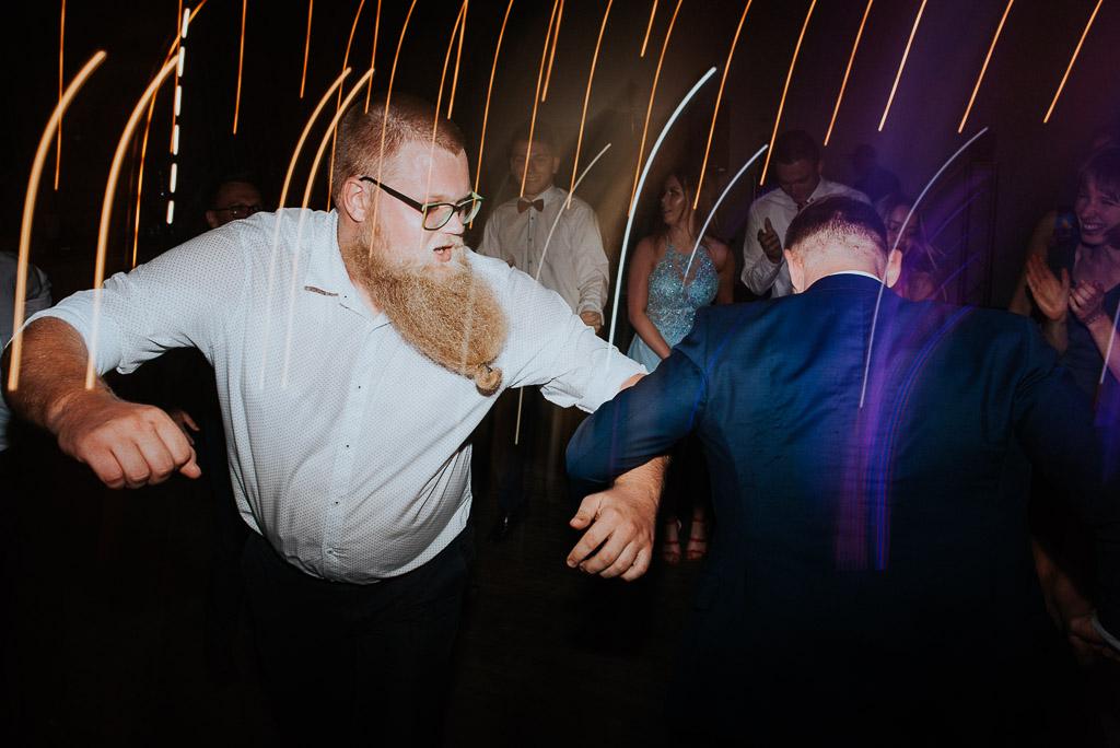 wesele sesja nad morzem mężczyzna z długą brodą tańczy z panem młodym