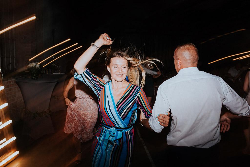 wesele sesja nad morzem kobieta w pasiastej sukience tańczy rozwianymi włosami