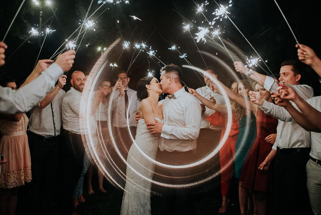 wesele sesja nad morzem całująca się para młoda pod szpalerem zimnych ogni
