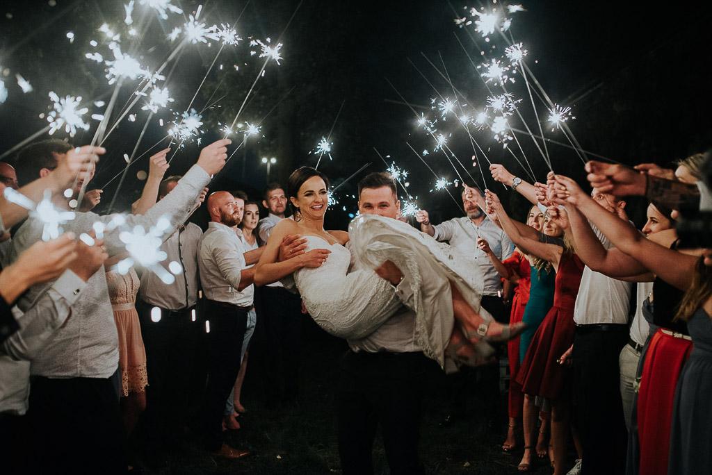 wesele sesja nad morzem pan młody niesie żonę w szpalerze zimnych ogni