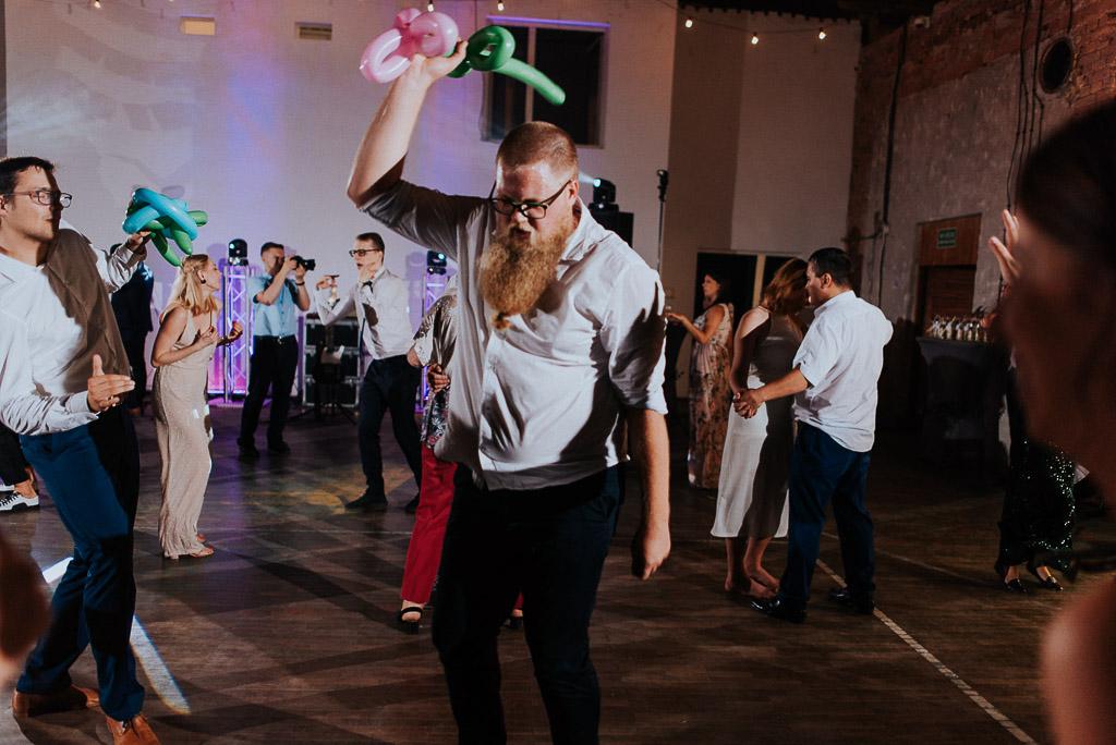 wesele sesja nad morzem gość weselny z długą brodą trzymający balony