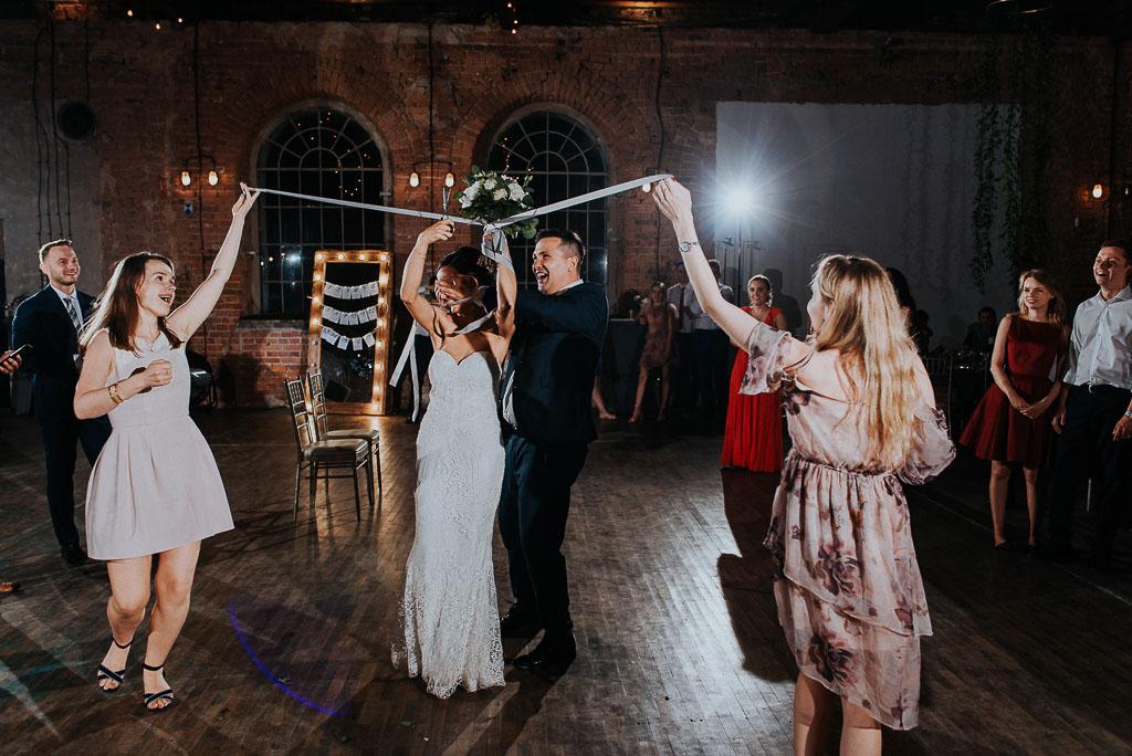 wesele sesja nad morzem oczepiny panna młoda odcina wstążki z bukietu