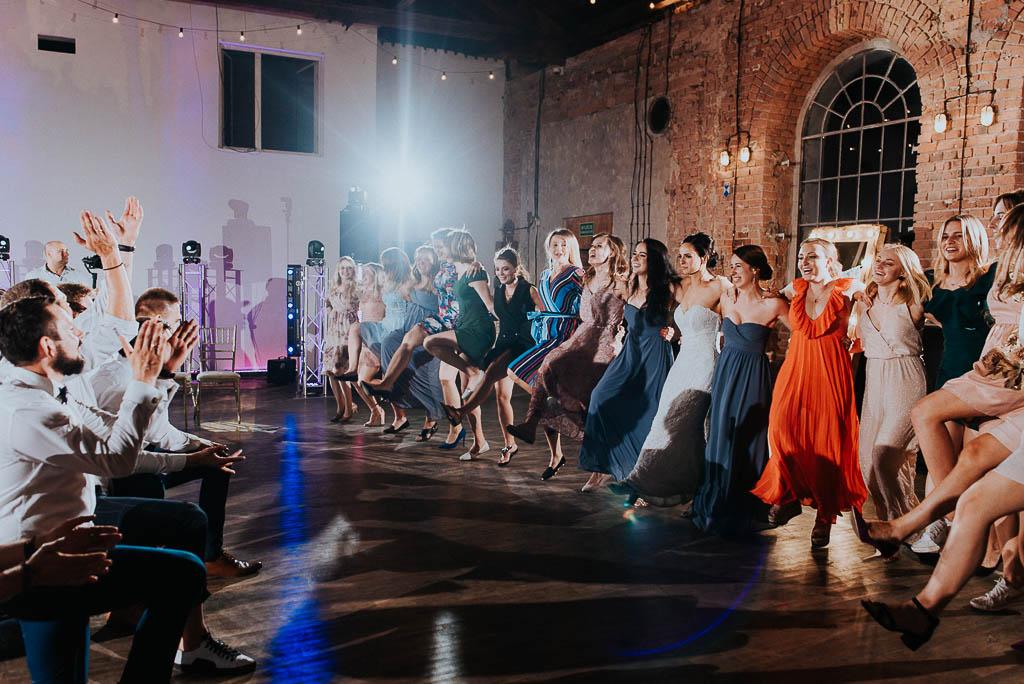 wesele sesja nad morzem kobiety tańczące kankana na oczepinach przed klęczącymi mężczyznami