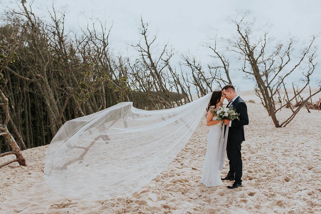 wesele sesja nad morzem para młoda na wydmach przytula się długi welon rozwiany