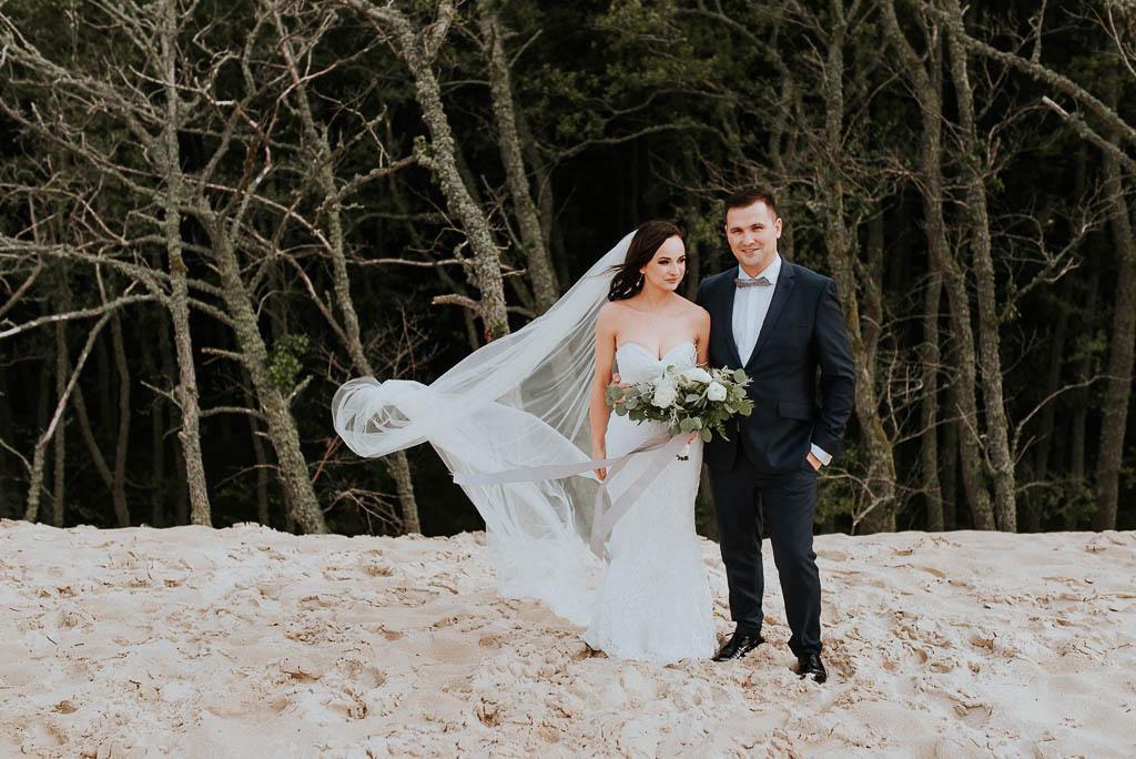 wesele sesja nad morzem para młoda spaceruje po wydmach wiatr rozwiewa długi welon