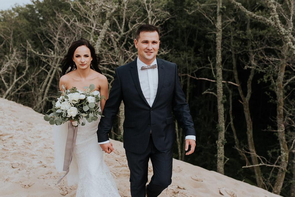 wesele sesja nad morzem para młoda trzymająca się za rękę idzie po wydmach