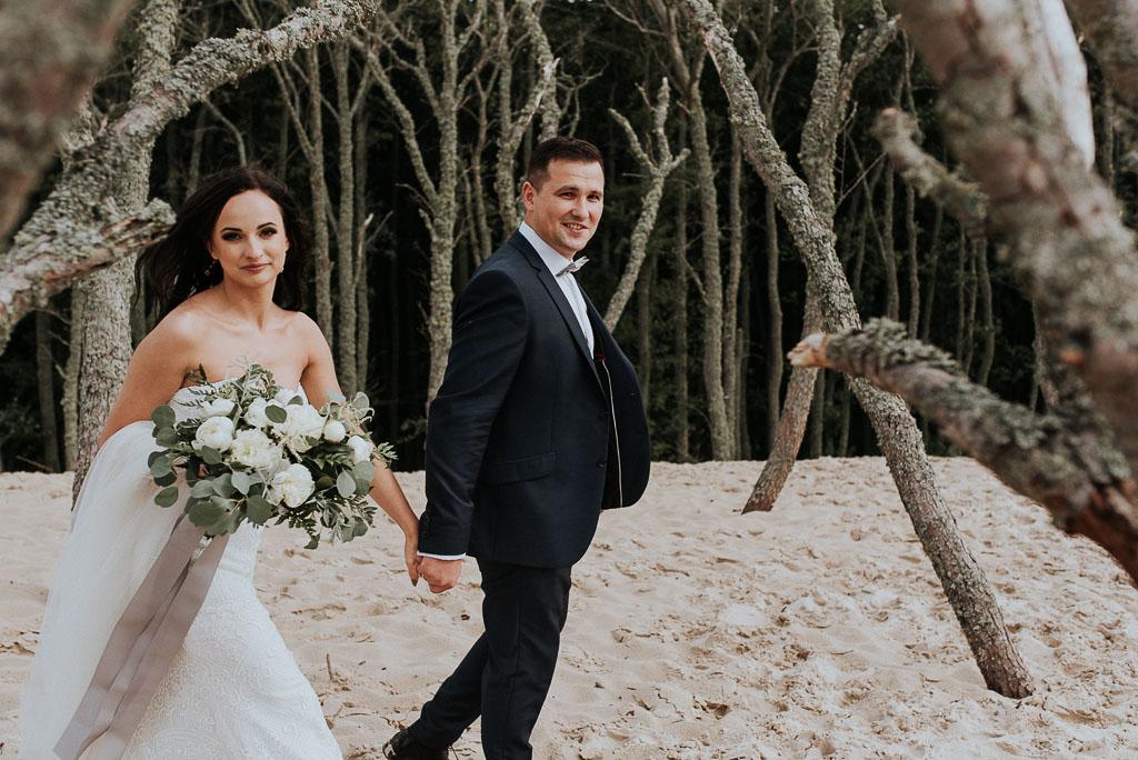 wesele sesja nad morzem spacerująca para młoda wśród uschniętych drzew