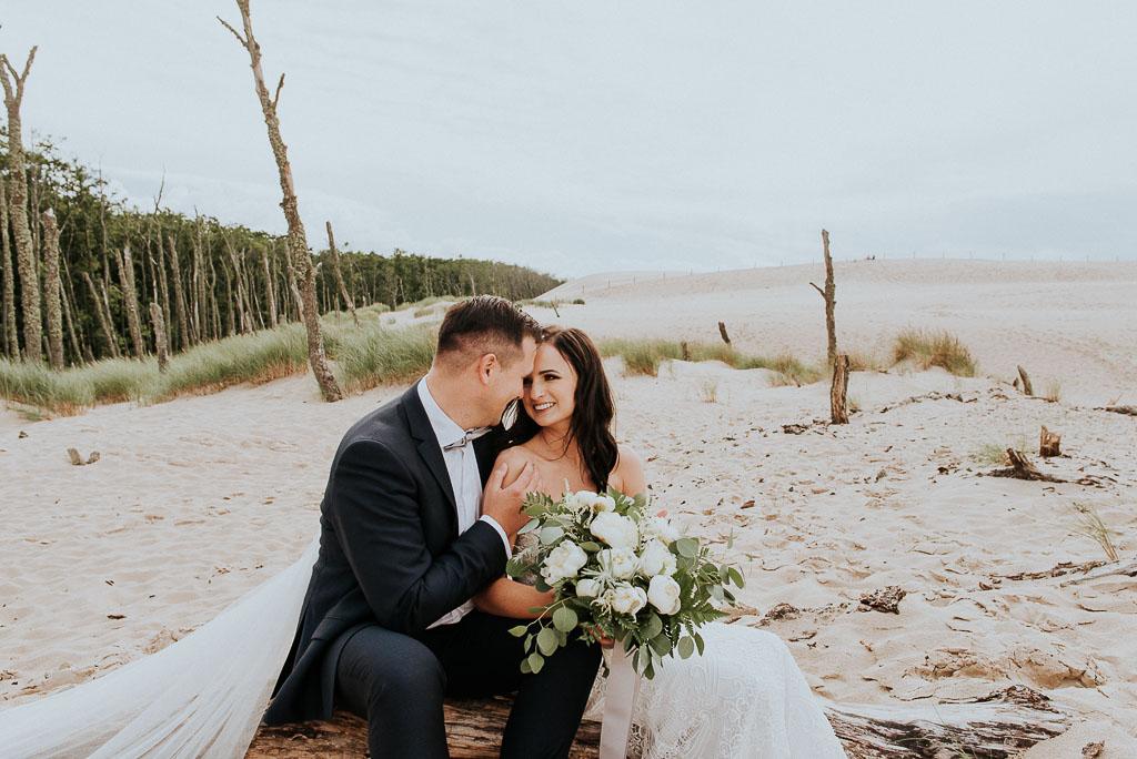 wesele sesja nad morzem para młoda siedzi na suchym pniu i przytula się