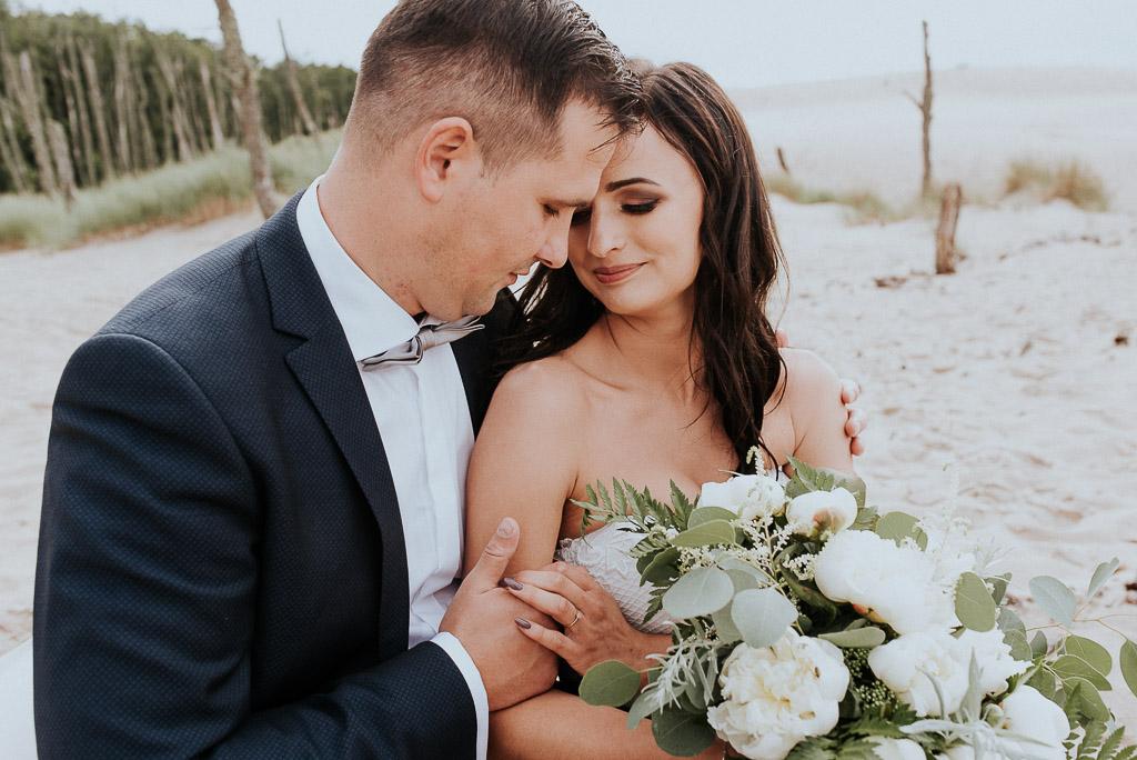 wesele sesja nad morzem zamyślona panna młoda w objęciach męża