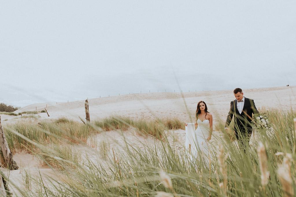 wesele sesja nad morzem para młoda spaceruje wśród traw na wydmach w łebie