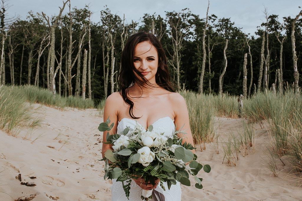 wesele sesja nad morzem panna młoda z rozwianymi włosami oraz bukietem kwiatów