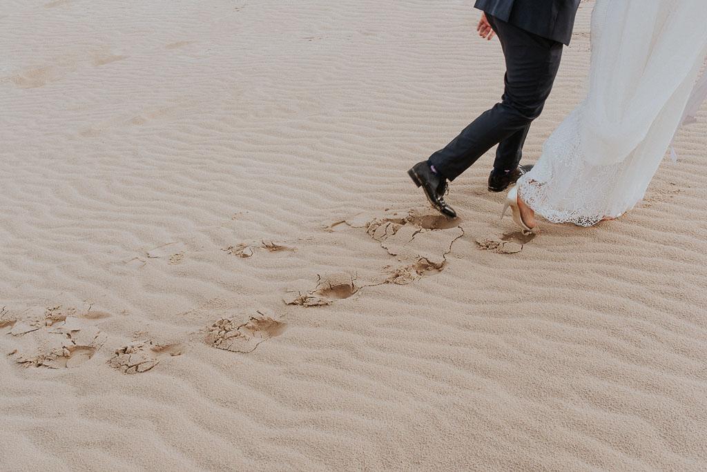 wesele sesja nad morzem ślady na piasku pozostawione przez buty młodej pary