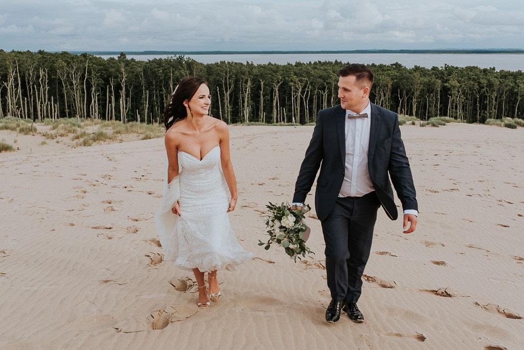 wesele sesja nad morzem pan młody niosący kwiaty patrzy na żonę