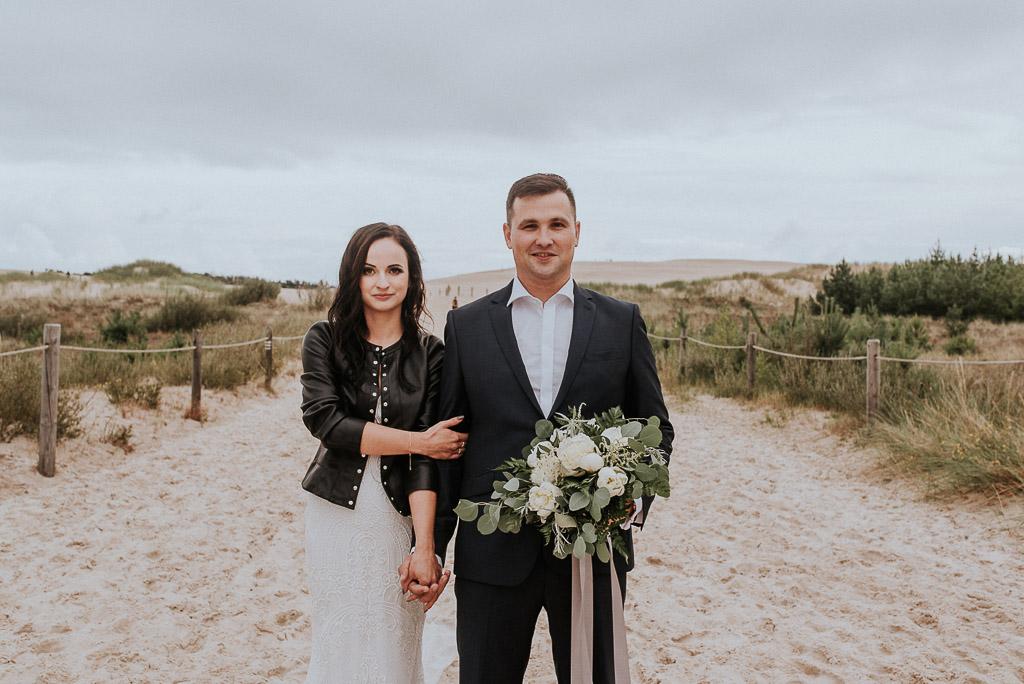 wesele sesja nad morzem panna młoda w skórzanej kurtce oraz pan młody z bukietem kwiatów trzymają cie za rękę