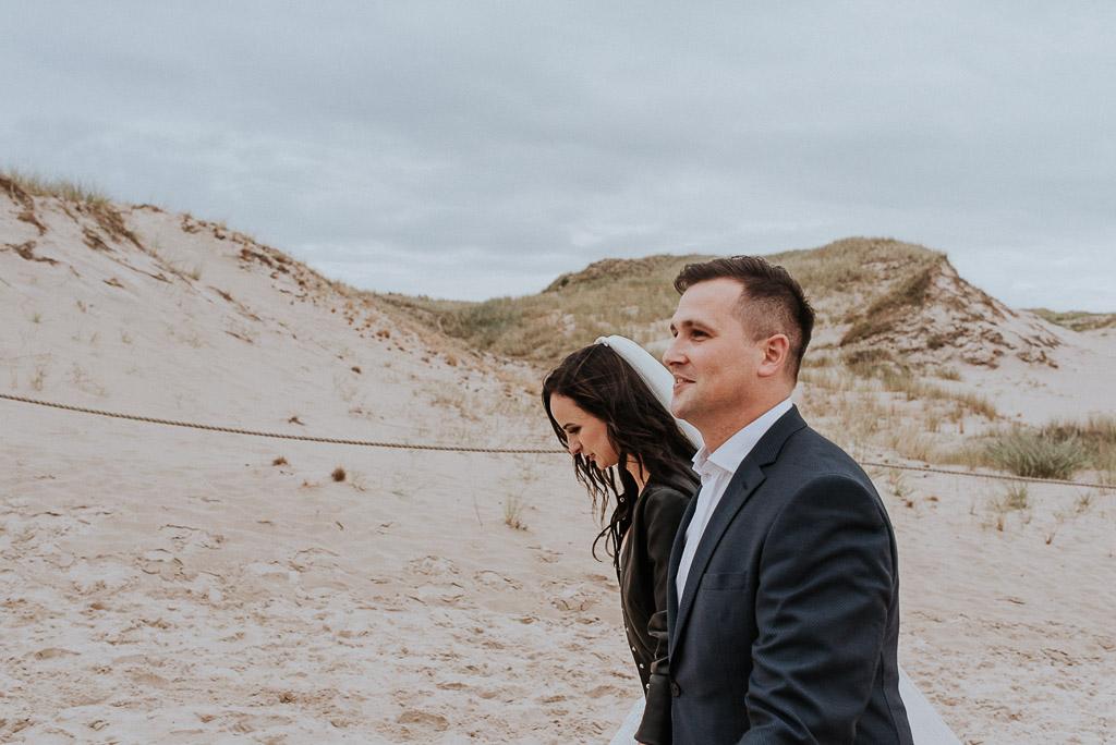 wesele sesja nad morzem panna młoda w skórzanej kurtce spaceruje z mężem