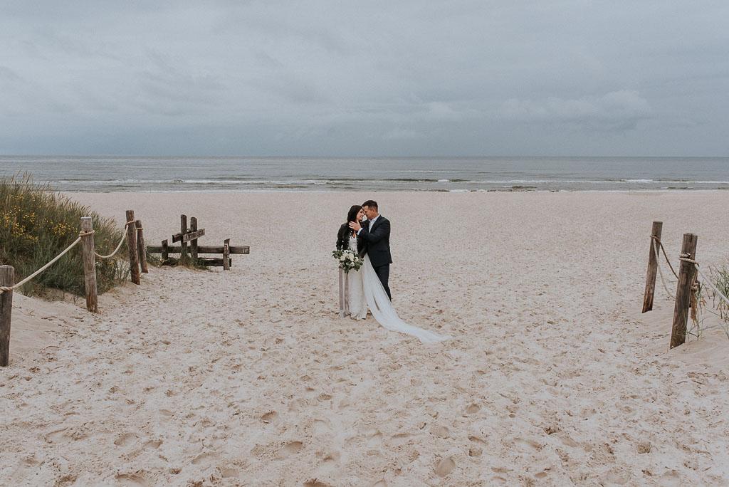 wesele sesja nad morzem młoda para całująca się na plaży z morzem w tle