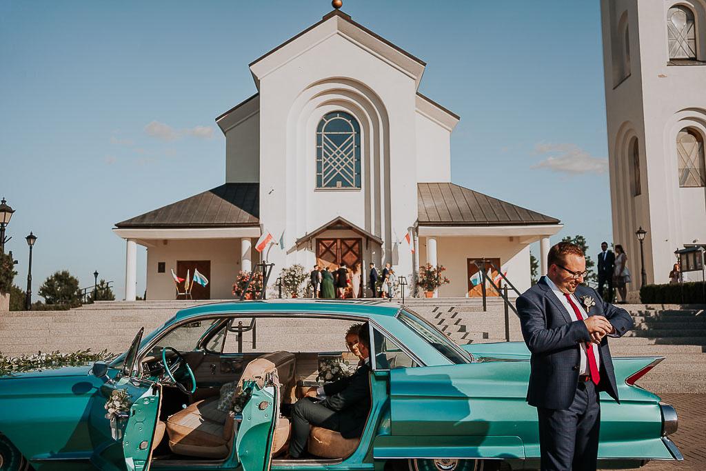 świadek zerka na zegarek przed kościołem