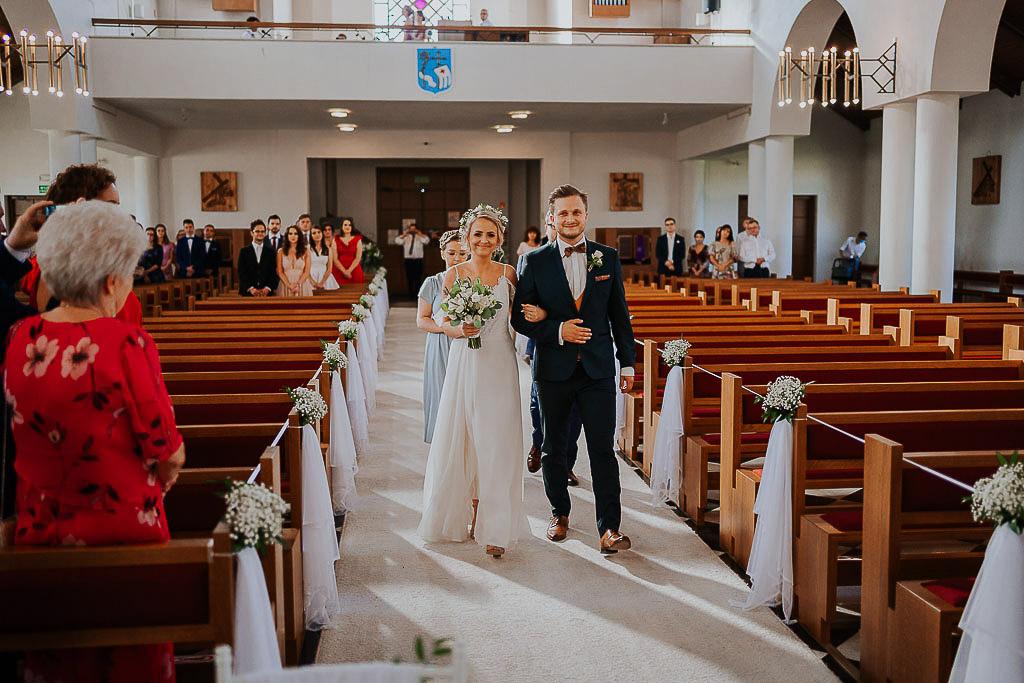 para młoda idzie w kościele po białym dywanie