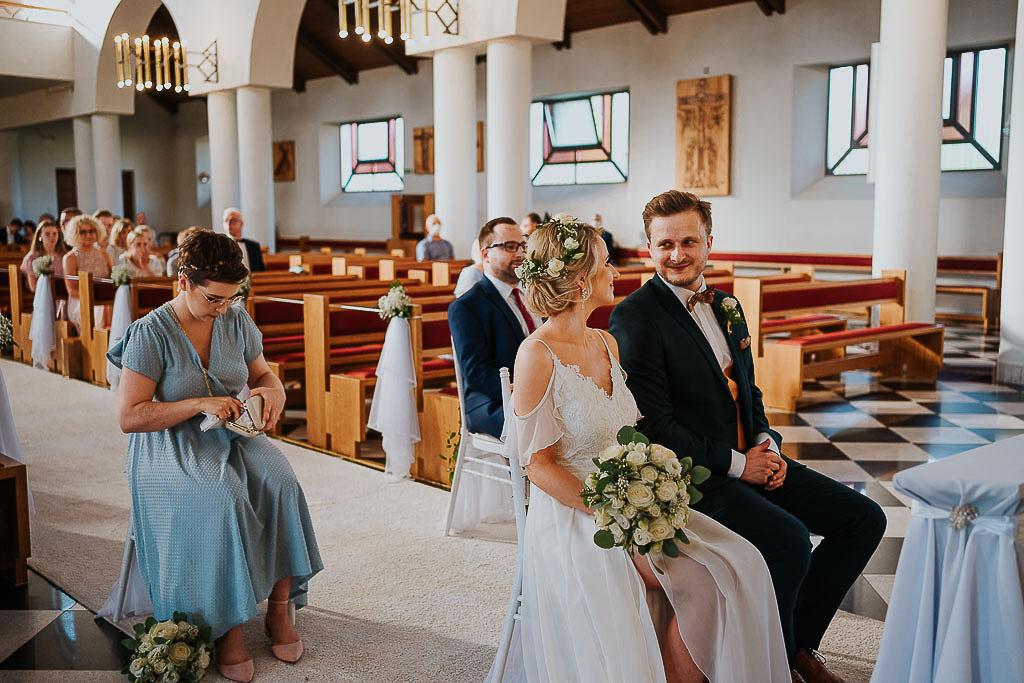 szczęśliwi nowożeńcy na białych krzesłach
