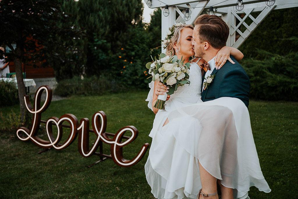 pan młody niosący żonę na rękach, pocałunek, napis love