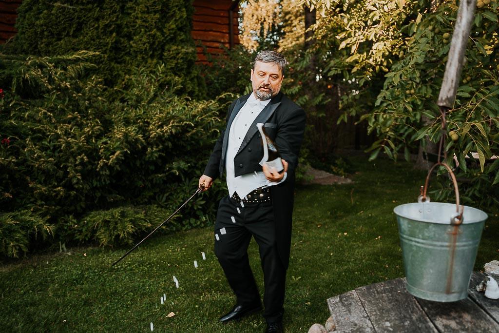 kipiący szampan tuż po otwarciu przez wodzireja za pomocą szabli chata za wsią