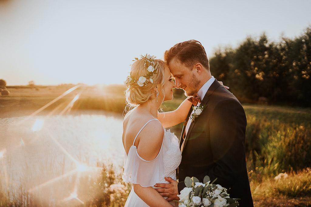 zakochana para młoda przytula się o zachodzie słońca stykając swoje czoła chata za wsią