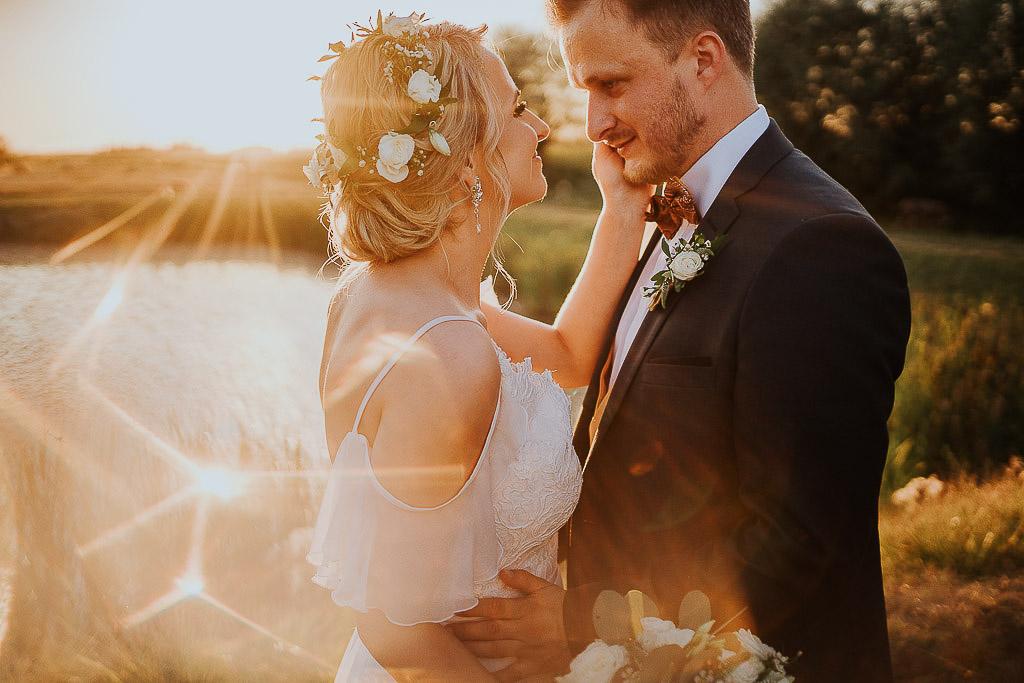 szczęśliwi nowożeńcy patrzą sobie w oczy chata za wsią