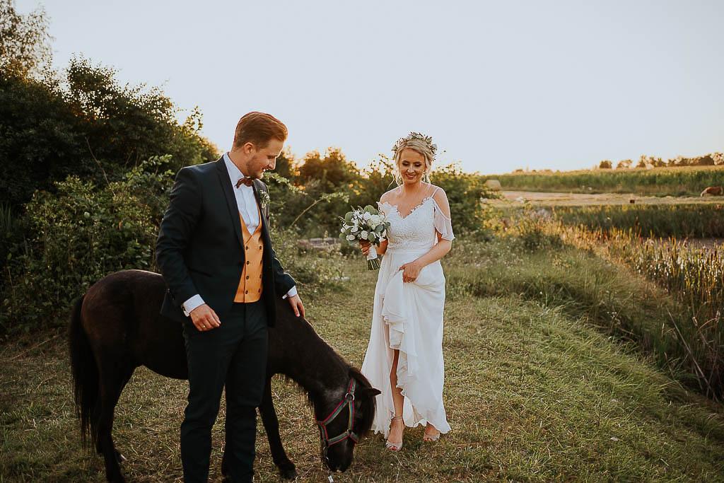 sesja ślubna z konikiem, panna młoda trzymająca bukiet chata za wsią