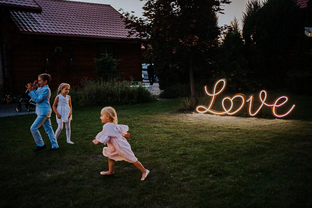 dzieci biegają po trawie, napis love w tle