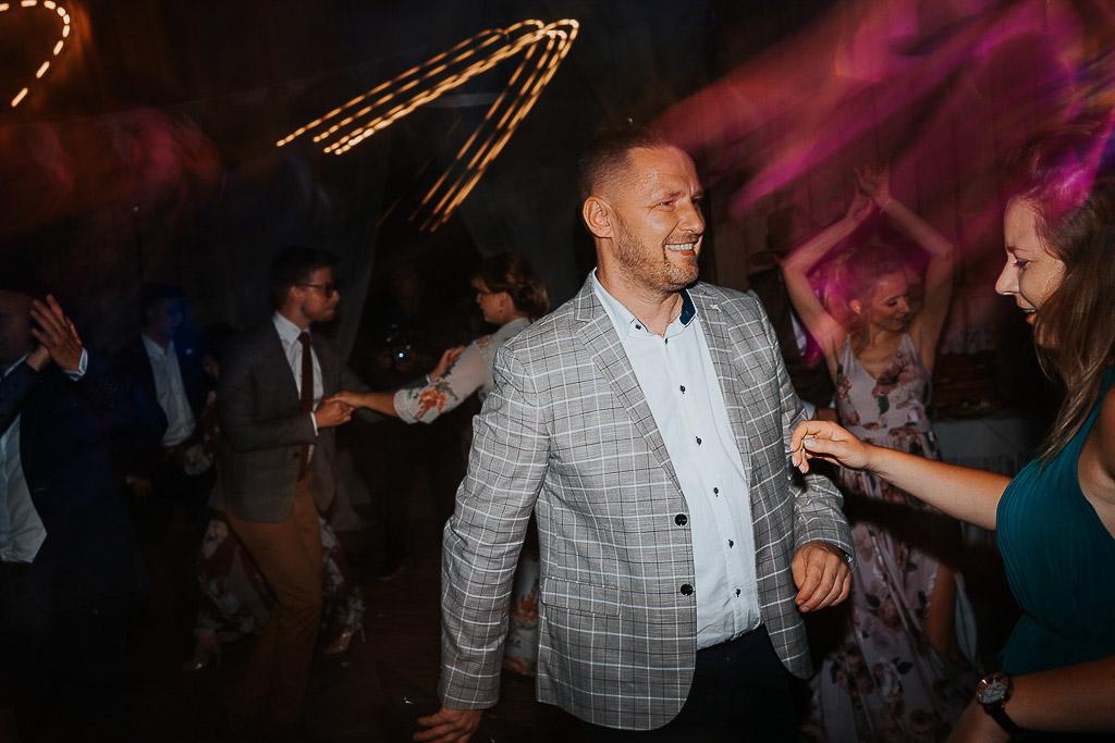 mężczyzna w garniturze w kratki tańczy z partnerka