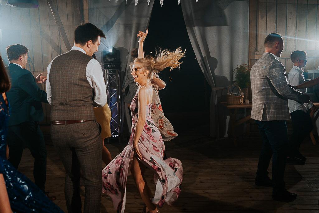 siostra panny młodej tańczy na parkiecie, włosy rozwiane chata za wsią