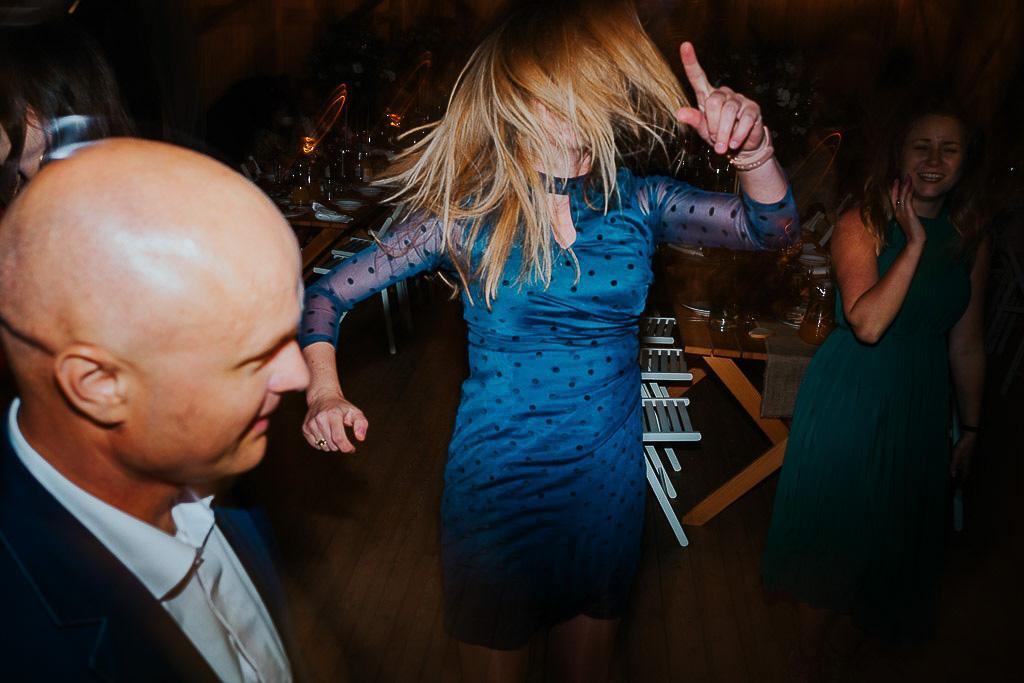 kobieta w niebieskiej sukience tańczy, włosy na twarzy