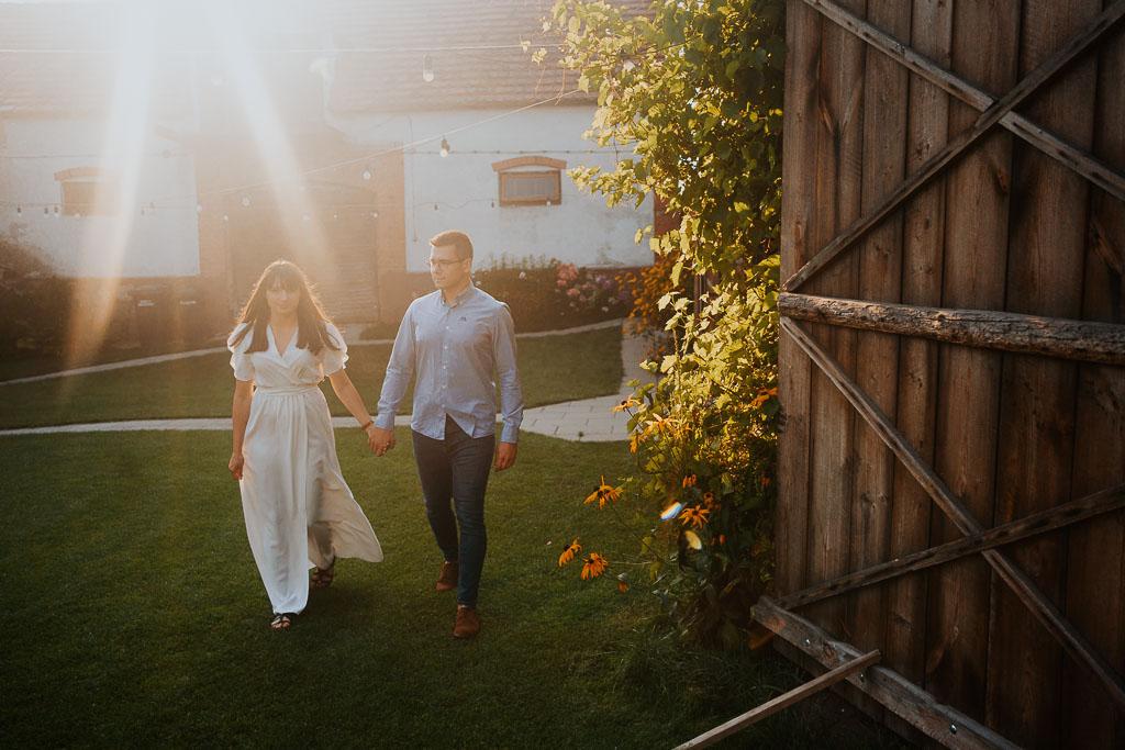 skompana w promieniach słońca para spaceruje w folwarku ruchenka