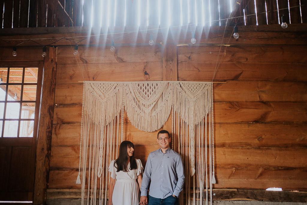 para w drewnianej stodole na tle makramy, słońce wpada przez szczeliny