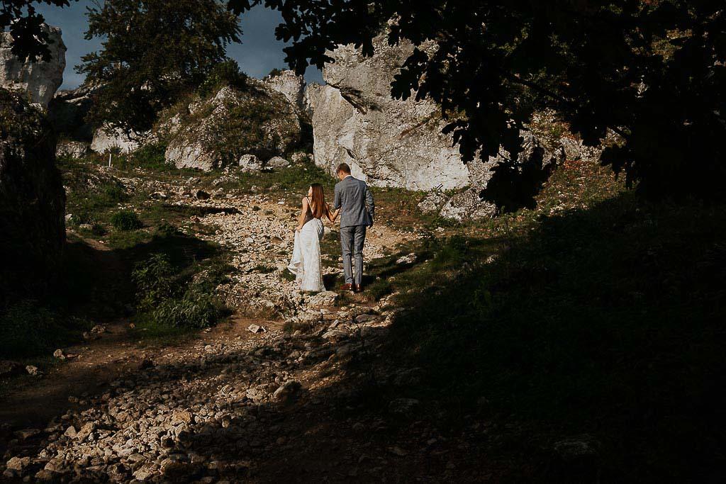 para młoda wspina się po kamienistej ścieżce na górę sesja w górach piotr czyżewski