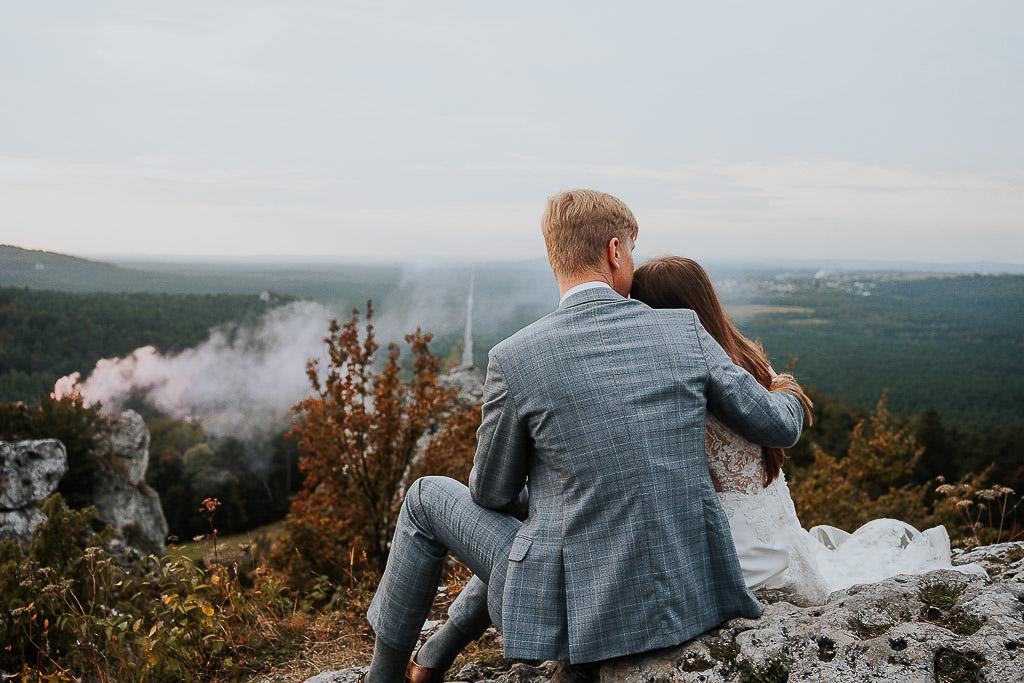 para młoda odwrócona plecami sieci na skale, różowy dym w tle sesja w górach piotr czyżewski