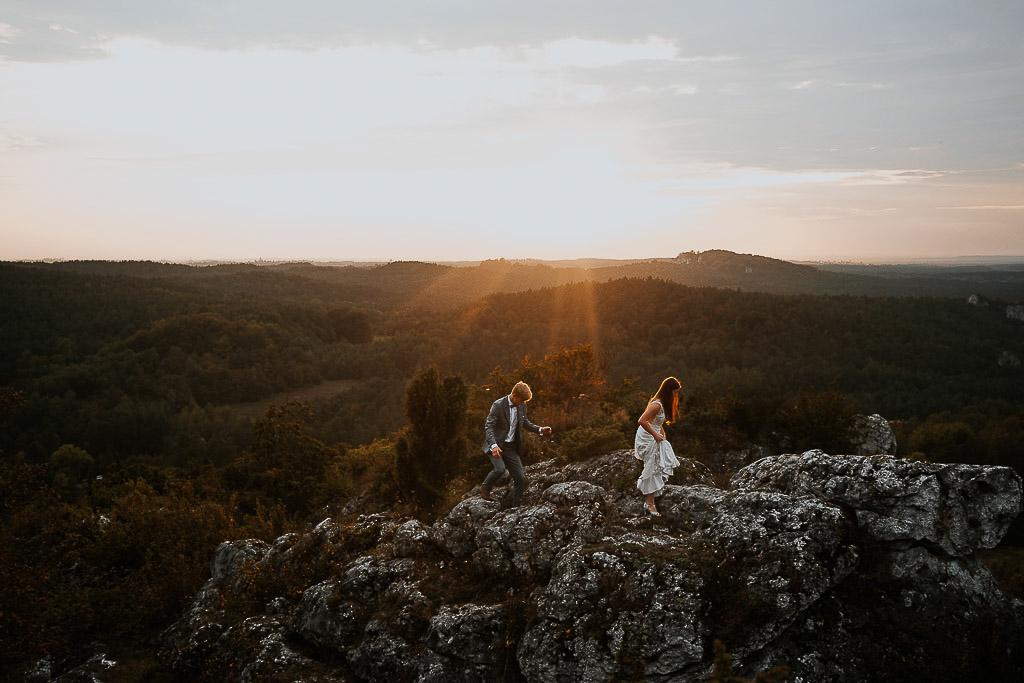 para młoda wspina się po skale przy zachodzącym słońcu sesja w górach piotr czyżewski