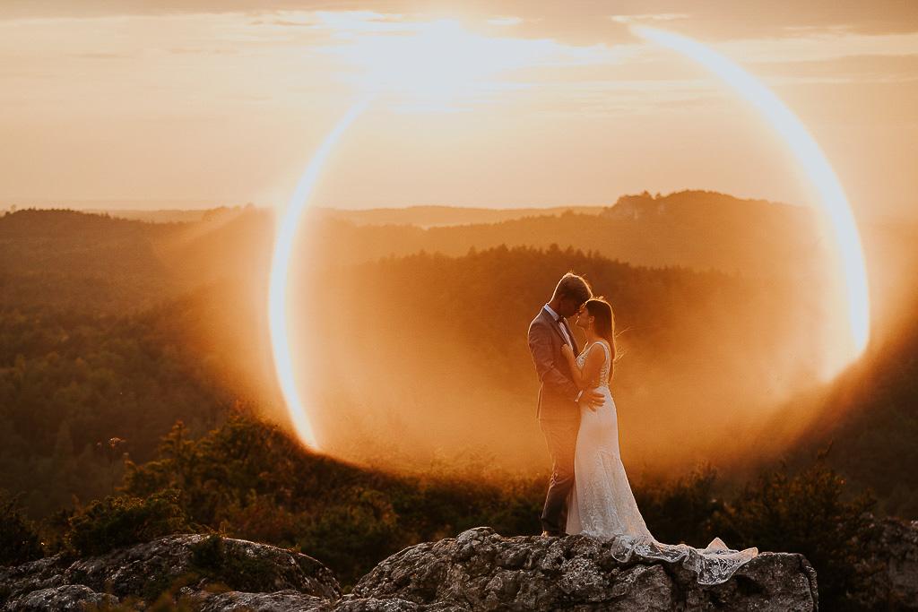 para młoda zamknięta w słonecznym pierścieniu na skale sesja w górach piotr czyżewski