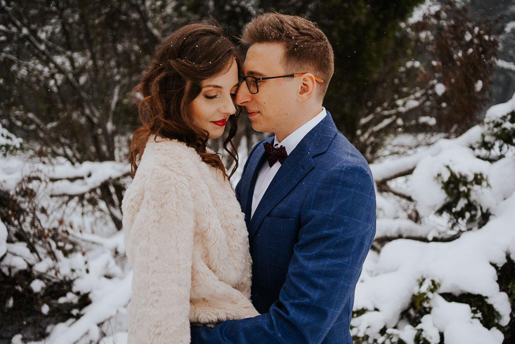przytulona para młoda, pan młody w okularach, czerwone usta zimowa sesja Piotr czyżewski fotografia
