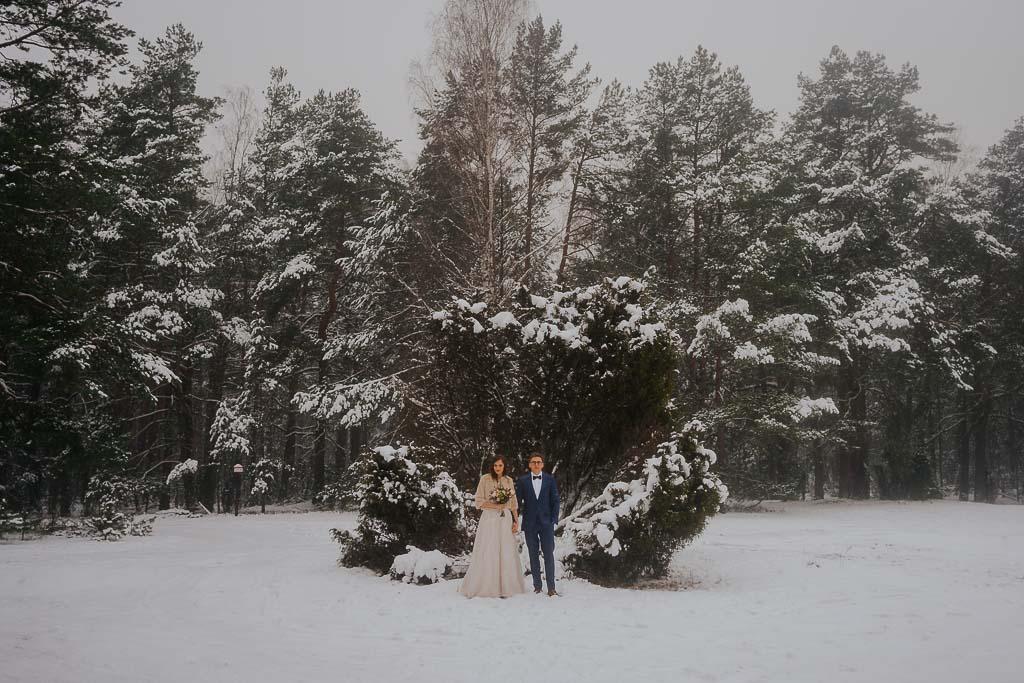 para młoda na tle drzew w lesie, zima, śnieg, zimowa sesja Piotr czyżewski fotografia