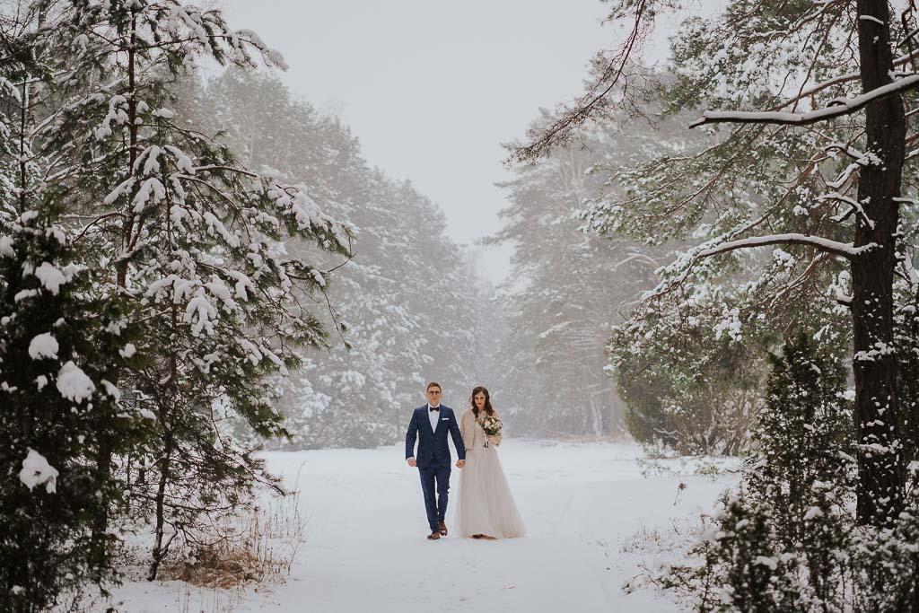 para młoda spaceruje zimą w lesie trzymając się za ręce zimowa sesja Piotr czyżewski fotografia