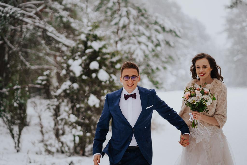 biegnące para młoda trzyma się za ręce zimowa sesja Piotr czyżewski fotografia