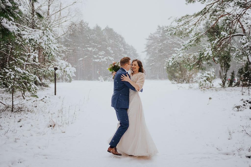 uśmiechnięta panna młoda w objęciach męża w lesie zimowa sesja Piotr czyżewski fotografia