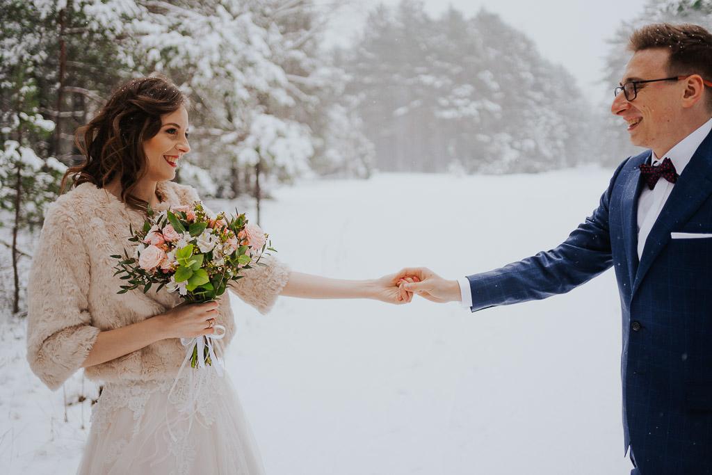 para młoda trzyma się za ręce zimą w lesie suknia ślubna z futerkiem zimowa sesja Piotr czyżewski fotografia