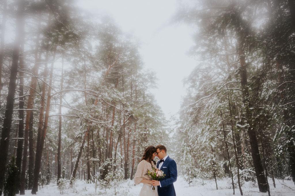 para młoda stykającą się czołami zimą w lesie, suknia z futrem zimowa sesja Piotr czyżewski fotografia