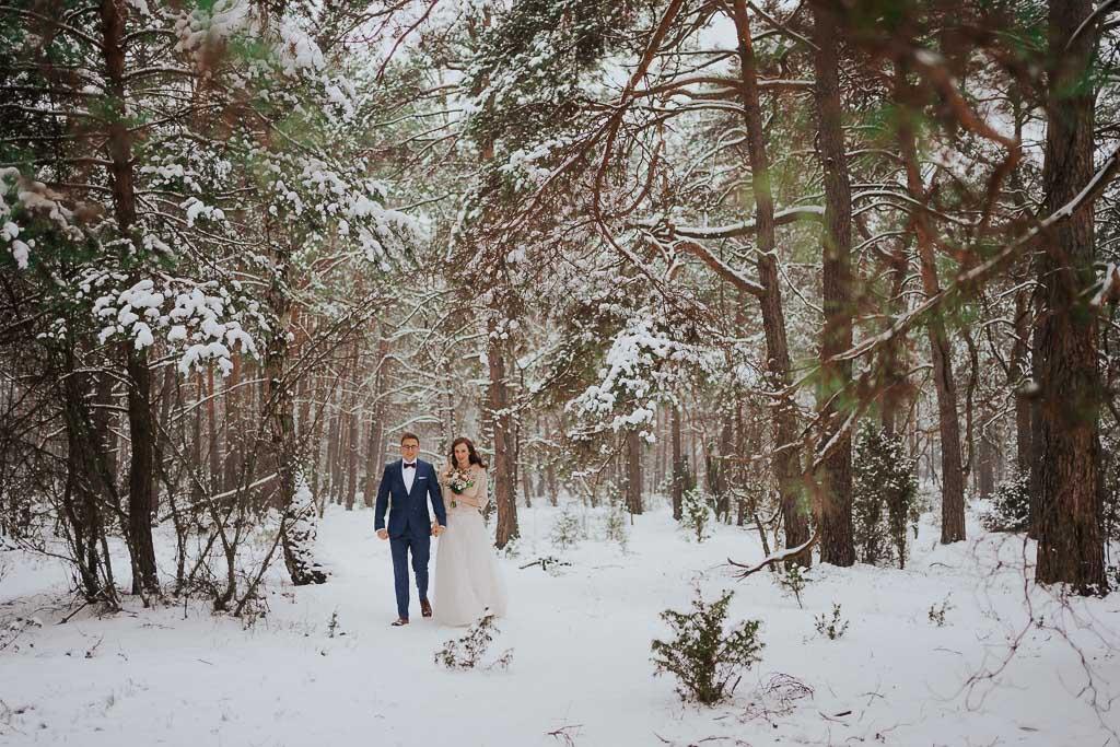 para młoda spaceruje przez zaśnieżony las zimowa sesja Piotr czyżewski fotografia